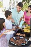 Familie, die einen Grill genießt Lizenzfreie Stockfotos
