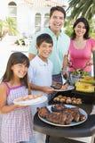 Familie, die einen Grill genießt Stockbild