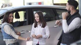 Familie, die einen Neuwagen kaufend feiert stock video