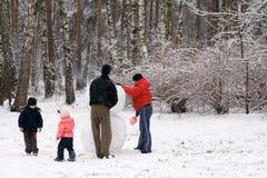 Familie, die einen Schnee-Mann formt Stockfotos