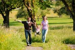 Familie, die einen Weg draußen im Sommer hat Stockbild