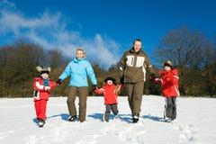 Familie, die einen Weg im Schnee hat Lizenzfreie Stockfotos