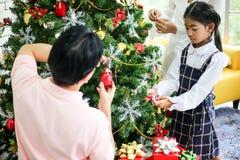 Familie, die einen Weihnachtsbaum verzieren und Vater, der Weihnachten G gibt lizenzfreies stockbild