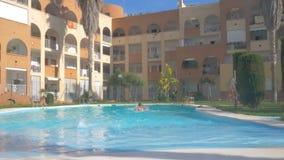 Familie die, en pret in de openluchtpool op zonnige dag hebben zwemmen duiken Jonge mooie vrouw in roze zwemmend kostuum en stock footage