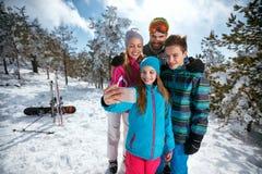 Familie die en selfie met mobiel op de winterski vacat glimlachen maken Stock Fotografie