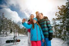Familie die en selfie met mobiel op vaca van de de winterski lachen maken Stock Afbeelding
