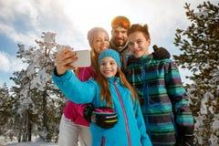 Familie die en selfie met smartphone op de winterski lachen maken Royalty-vrije Stock Afbeeldingen