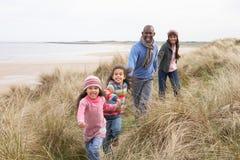 Familie, die entlang Dünen auf Winter-Strand geht Lizenzfreie Stockbilder