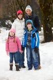 Familie, die entlang Snowy-Straße im Skiort geht Lizenzfreie Stockfotos