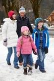 Familie, die entlang Snowy-Straße im Skiort geht Stockfoto