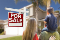 Familie, die für Verkaufs-Real Estate-Zeichen und -haus gegenüberstellt Stockfotos