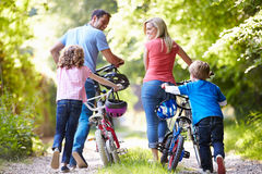 Familie, die Fahrräder entlang Land-Bahn drückt Stockfotografie