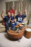 Familie, die Fernsehdas zujubeln überwacht Lizenzfreie Stockbilder