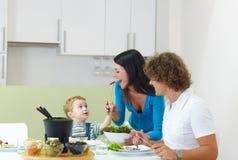 Familie, die Fleischfondue isst Stockfotografie