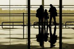 Familie, die am Flughafen wartet Stockfotos