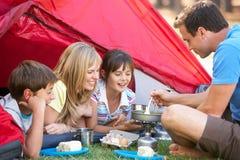Familie, die Frühstück an kampierendem Feiertag kocht Stockfotos