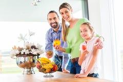 Familie, die frische Früchte für gesundes Leben in der Küche isst Lizenzfreie Stockfotos