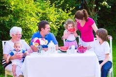 Familie, die Frucht im Garten isst Lizenzfreie Stockbilder