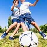 Familie, die Fußball im Park im Sommer spielt Lizenzfreie Stockbilder