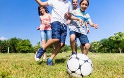 Familie, die Fußball oder Fußball im Park spielt Stockfotos