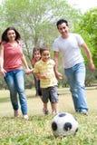 Familie, die Fußball spielt und Spaß hat Stockbild