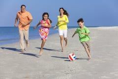 Familie, die Fußball-Fußball auf Strand spielt Stockfoto