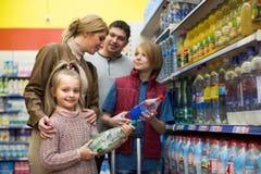 Familie, die funkelndes Wasser im Speicher kauft Stockbild