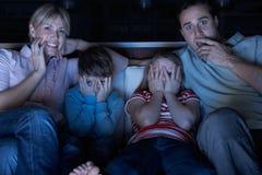 Familie, die furchtsames Programm über Fernsehapparat sich ansieht Stockbild