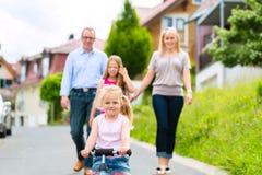 Familie die gang voor huizen in dorp hebben royalty-vrije stock afbeelding