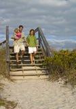 Familie, die geht auf den Strand zu setzen Lizenzfreie Stockbilder