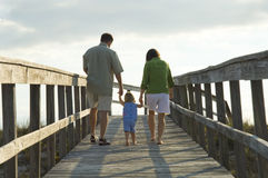 Familie, die geht auf den Strand zu setzen
