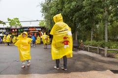 Familie, die gelbe Legoland-Ponchos trägt Stockfotografie