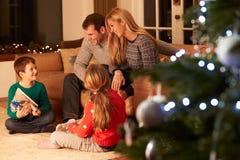 Familie, die Geschenke durch Weihnachtsbaum austauscht Lizenzfreie Stockfotografie