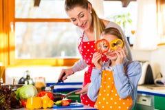 Familie, die gesundes Lebensmittel mit Spaß kocht Lizenzfreie Stockfotografie
