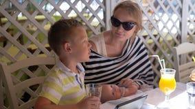 Familie die goede dag hebben Moeder met baby en het oudere zoon ontspannen in koffie stock video