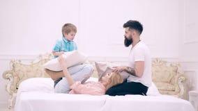 Familie die grappige hoofdkussenstrijd op bed hebben Ouders die vrije tijd met hun zoon doorbrengen De gelukkige familie heeft bi stock videobeelden