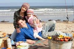 Familie, die Grill auf Winter-Strand hat Lizenzfreies Stockfoto