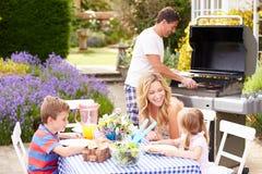 Familie, die Grill im Freien im Garten genießt Stockbild