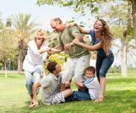 Familie die grootvader tegenhoudt en pret heeft Royalty-vrije Stock Foto's