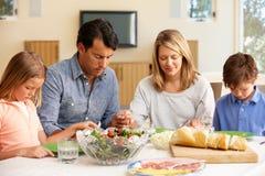Familie die gunst zegt vóór maaltijd Stock Afbeeldingen