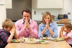Familie die gunst zegt vóór maaltijd Stock Foto