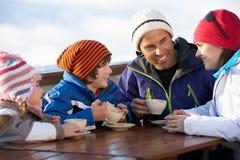 Familie, die heißes Getränk im Kaffee am Skiort genießt Stockbild