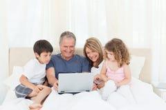 Familie die hun laptop bekijkt Royalty-vrije Stock Afbeeldingen