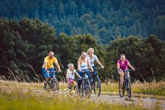 Familie, die ihr Fahrrad am Nachmittag in der Landschaft fährt Stockbild