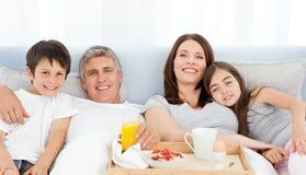 Familie, die in ihrem Bett frühstückt Lizenzfreie Stockfotos