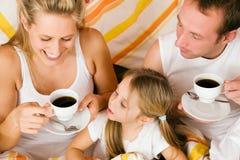 Familie, die im Bett frühstückt Lizenzfreie Stockbilder