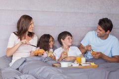 Familie, die im Bett frühstückt Stockbilder