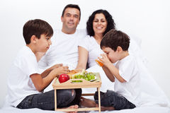 Familie, die im Bett frühstückt Stockfotografie