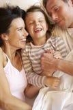 Familie, die im Bett sich entspannt stockbilder