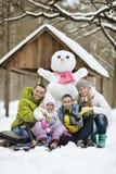 Familie, die im frischen Schnee spielt Stockfotografie